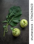 Small photo of Kohlrabi and kohlrabi leaves on a dark background