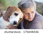Stock photo senior woman hugs her beagle dog in countryside 170648336