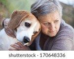 Stock photo senior woman hugs her beagle dog in countryside 170648336