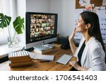 Small photo of Riga, Latvia - March 28 2020: Young woman having video Zoom call via computer in the home office. Remote teem meeting Stay at home and work from home concept. Manage Online office