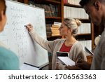 Small photo of Young woman solving mathematics problem on whiteboard. College student solving algebra equation on white board in library with students. Girl trying to understand mathematics problem during lesson.