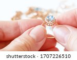 Small photo of hand takes ring with big blue topaz and white diamonds around on other jewerly background, jewerly inspect and verify, pawnshop concept