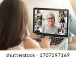 Small photo of Laptop screen view mature 50s lady lead group videocall distant talk with different ethnicity age women. View over girl shoulder sit on sofa involved at remote chat, empowerment movement club concept