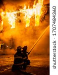 Firefighters Use A Fire Hose To ...