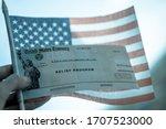 COVID-19 economic Stimulus check on blurred USA flag background. Relief program concept.  - stock photo