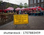 """Small photo of BREDA - APRIL 2: warning sign against coronavirus at market on 2 April 2020, in Breda,The Netherlands. Translation:""""together against CORONA. Abide the rules.1,5 meter distance. More info:www.breda.nl"""""""