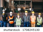 Small photo of Group of industrial or engineer corporate workers wear protective mask and hard hat helmet standing line up in front of factory lock down prevention for Coronavirus or COVID-19 epidemic outbreak