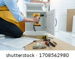Small photo of close up man holding cordless screwdriver machine and screws lie for screwing a screw assembling furniture at home