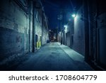 Small photo of Dark and eerie urban city alley at night