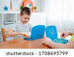 Small photo of Boy child with dad playing warships and submarines are placed on the playing field in the game battleship. entertainment Board games at home in self-isolation in quarantine. Sea battle