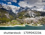 Small photo of The Improbable aerial landscape of village Molveno, Italy, azure water of lake, empty beach, snow covered mountains Dolomites on background, roof top of chalet, sunny weather, a piers, coastline