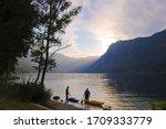 Two men preparing for kayaking in Lake Bohinj in Slovenia - stock photo