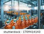 Conveyor belt, juice in bottles, beverage factory interior in blue color, industrial production line.