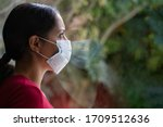 Small photo of Young sad woman wearing a face mask looking through the window with her reflection on the glass, self isolated at home. Coronavirus and Quarentine concept