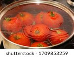Red blanched tomatoes in a metal pot