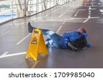 Small photo of Inattentive man has fallen down on wet floor in spite of the big yellow warning sign