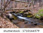 A Stream Runs Under A Wooden...