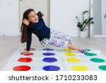 Small photo of little girl playing on a twister game at home. Girl smiles and looks up