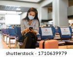 Small photo of Young Asian tourist woman with mask using phone and sitting with distance at the airport