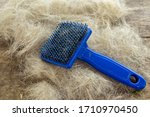 Small photo of Bunch of dog hair after grooming and cleaning with blue slicker on wooden table