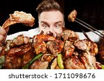 Small photo of Crazy hungry man eating mix grill meat. Emotional content for restaurant promo. Cheat day. Meat lover. Lamb chops, chicken tikka, kebab, lamb, beef steak.