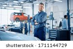 Handsome Car Mechanic is Posing in a Car Service. He Wears a Jeans Shirt and Safety Glasses. His Arms are Crossed. Specialist Looks at a Camera and Smiles. - stock photo