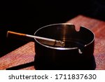 Small photo of Burning cigarette in metal ashtray. Burning in a cigarette ashtray harmful to health. cigarette in iron ashtray.