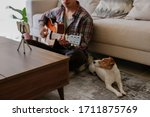 Small photo of Musician practicing acoustic guitar exercises, taking online musical courses, reading notes from phone on tripod & a pet friend listening his music. Jack Russell Terrier puppy. Background, close up.