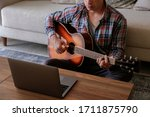 Music college hipster student practicing acoustic guitar exercise, reading notes from laptop computer. Man taking an online musical courses at home during quarantine. Background, close up - stock photo