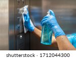 Small photo of Hand in blue surgical gloves using disinfectant from the bottle spraying an elevator push button control panel.Disinfection,cleanliness and healthcare,Anti bacterial and Corona virus (COVID-19).
