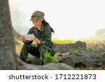 Beautiful soldier read the letter with happy emotion in the border line of battle field during war. - stock photo