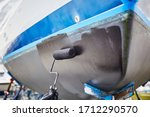Person painting a boat's bottom with a fresh paint, using roller and black paint, outdoors in the boatyard - stock photo