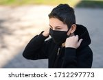 teen in a black medical mask on the street - stock photo