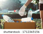Small photo of Volunteer woman keep plastic bottle into paper box at public park,Dispose recycle and waste management concept,Good conscious mind