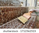 Small photo of Close up hand in glove use brush to remove unsightly surface rust from the staircase.