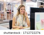 Small photo of Smiling mid woman working as customer support operator with headset in a call center. Portrait of happy sales agent sitting at desk and looking at camera. Customer care support service representative.