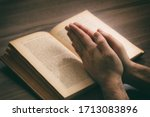 Small photo of Prayer, man hands over an open book Holy Bible, wooden desk background. Faith, religion gospel and spirituality concept