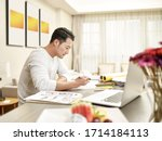 Small photo of young asian man design professional sitting at kitchen counter working from home (artwork in background digitally altered)