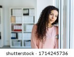 Small photo of Young woman staring longingly through a window with a sad faraway expression as she leans against a wall in an office
