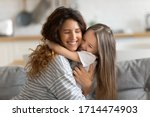 Small photo of Affectionate beautiful young woman cuddling small preschool child daughter, feeling happiness. Cute little kid girl embracing loving mommy, feeling thankful, enjoying tender sweet time at home.