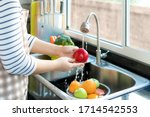 Small photo of Asian healthy woman washing an apple and other fruit above kitchen sink and cleaning a fruit / vegetable with water to eliminate the chances of contamination COVID-19.