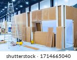 Installation of plywood partitions in the exhibition hall. Installation of plywood frames. Division of space. Zoning of space. Construction work. Renovation in the exhibition hall. - stock photo