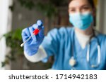 Small photo of Female caucasian doctor holding a swab collection stick, nasal and oral specimen swabbing in doctor's office, patient PCR testing procedure appointment, Coronavirus COVID-19 global pandemic crisis