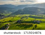 Small photo of Aerial view of improbable green meadows of Italian Alps, green slopes of the mountains, Bolzano, huge clouds over a valley, roof tops of houses, Dolomites on background, sunshines through clouds