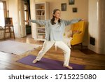 Small photo of Full length shot of happy energetic mature woman in casual clothes exercising at home because of social distancing, practicing yoga on mat, standing in warrior ii pose. Age, wellness and health