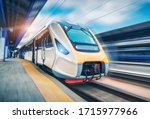 Small photo of High speed train in motion on the railway station at sunset. Modern intercity passenger train with motion blur effect on the railway platform. Industrial. Railroad in Europe. Commercial transportation