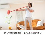 Handsome man cleaning his house ...