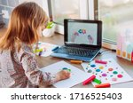 Small photo of Beautiful toddler girl molding colorful clay cloud with rain watching online learning lesson on the laptop indoor. Distance home learning concept.