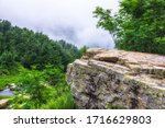 Stone rock among lush greenery on a foggy hillside with a mountain river. Heavy fog in the mountains on a cloudy day