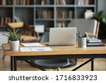 Wooden work desk with laptop and documents, books, modern interior of cozy cabinet, table for businessman or student at home, comfortable workspace, workplace with computer in apartment - stock photo